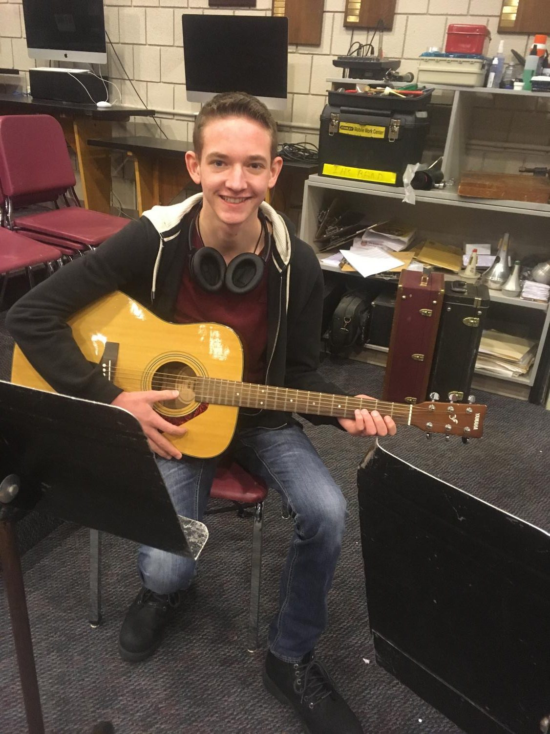 Senior Bradley Mcdowell sitting with his guitar