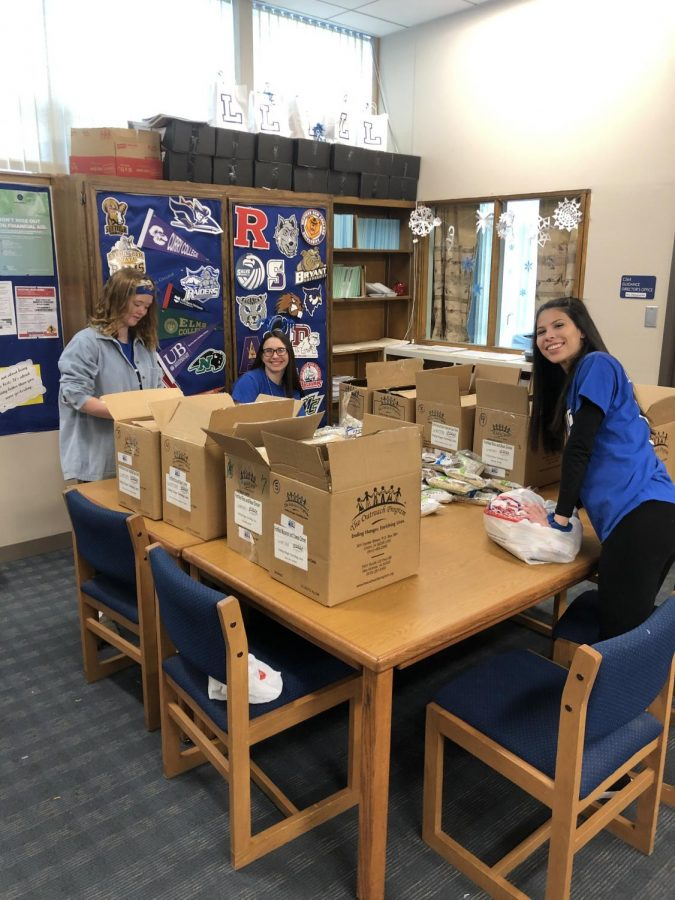 Mairead Durkan, Hailey McGinnis, and Lexis Bonilla work in the LHS Guidance Department to make food packages for food insecure students before the long vacation.